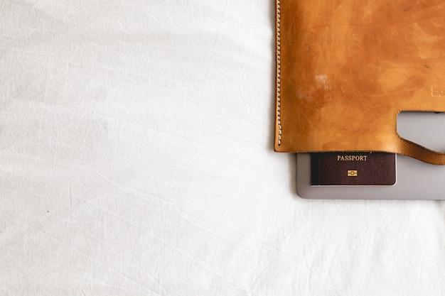 Mala de couro com passaporte e laptop no conceito de viagens de negócios. Foto Premium