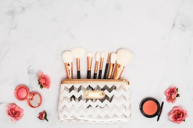 Mala de maquiagem branca com pincéis; pó compacto e rosas no pano de fundo texturizado Foto gratuita