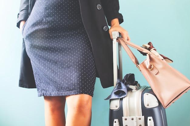 Mala de viagem e bolsa de viagem levando da mulher de negócios no fundo azul da cor, seção mestra. Foto Premium