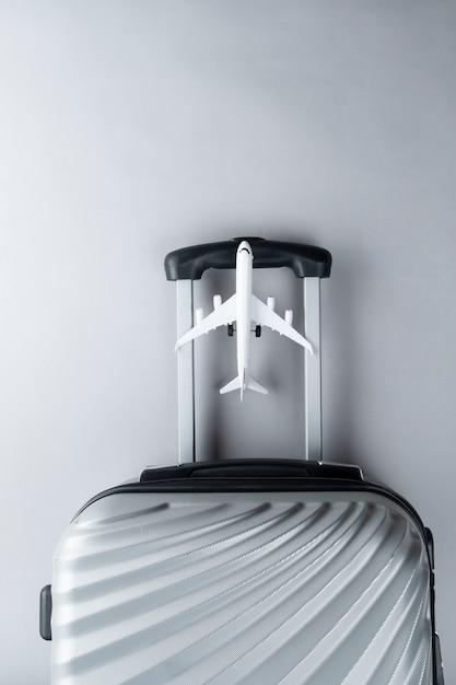 Maleta cinzenta lisa da configuração com mini avião. conceito de viagem Foto Premium
