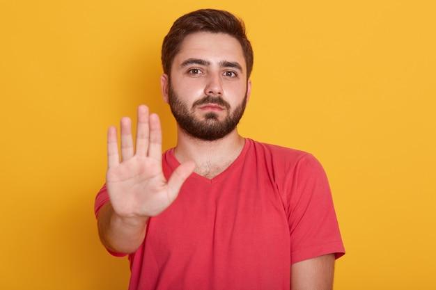 Malm barbudo jovem vestindo camiseta casual vermelha em pé com parada aviso gesto mão e olhando para a câmera com cara séria Foto gratuita