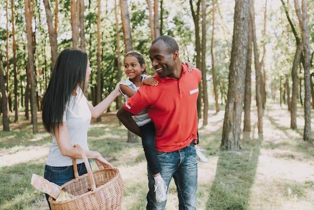 Mamã com balde de piquenique. pai com a filha nas costas. Foto Premium