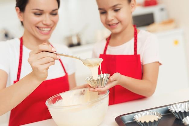 Mamãe arruma a massa no cortador de biscoitos. Foto Premium