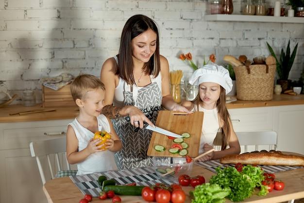 Mamãe cozinha o almoço com as crianças. uma mulher ensina sua filha a cozinhar com seu filho. vegetarianismo e alimentação natural saudável Foto Premium