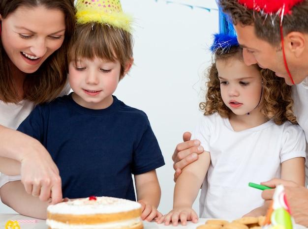 Mamãe e filho cortando um bolo de aniversário juntos Foto Premium