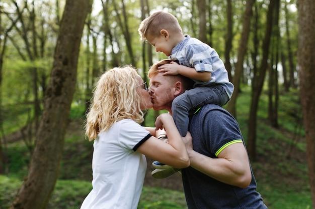 Mamãe e papai beijam enquanto seu filhinho fecha os olhos Foto gratuita