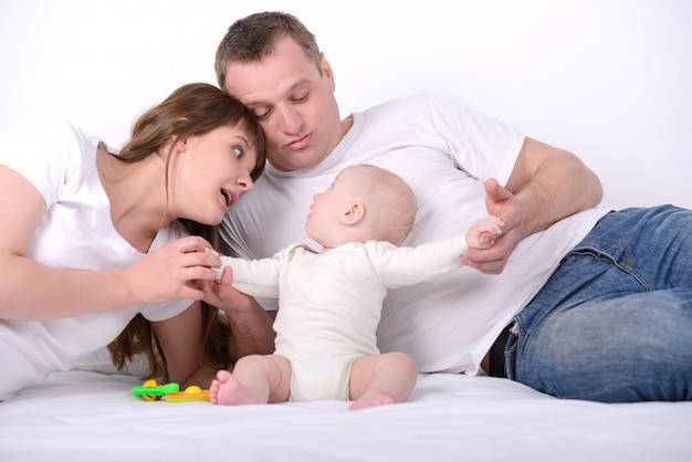 Mamãe e papai juntos com uma criança pequena na cama. Foto Premium
