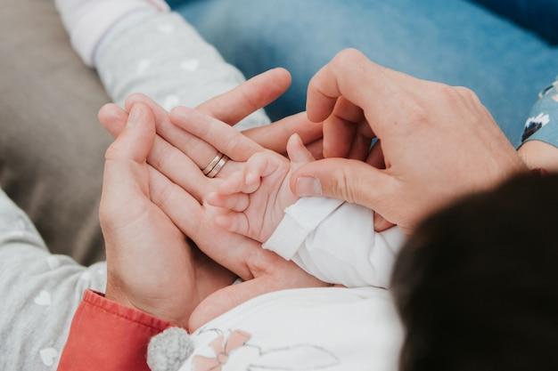 Mamãe e papai seguram a mão do bebê. puxador infantil Foto Premium