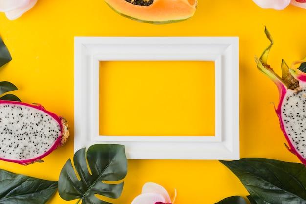 Mamão; fruta do dragão; deixa em torno do quadro de borda branca vazia contra pano de fundo amarelo Foto gratuita