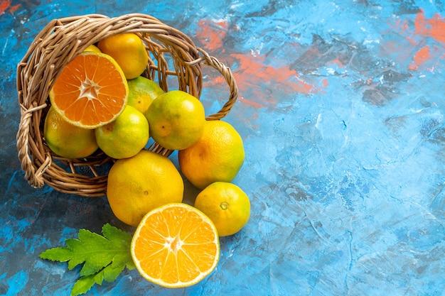 Mandarinas frescas de vista frontal em uma cesta de vime na superfície azul com espaço de cópia Foto gratuita