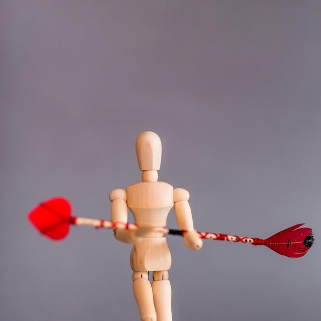 Manequim de madeira segurando a flecha de amor Foto gratuita