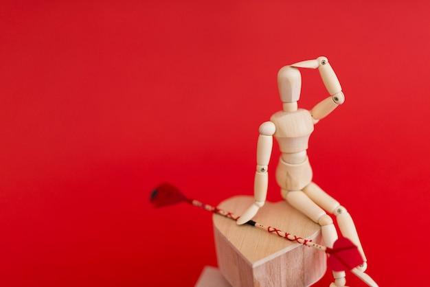 Manequim de madeira sentado no coração com flecha de amor Foto gratuita