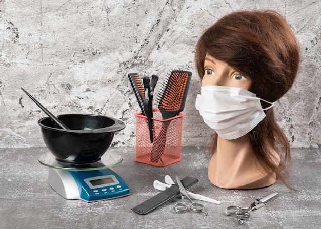 Manequim no rosto de máscara, escalas e tigela com ferramentas de escova e cabeleireiro Foto Premium