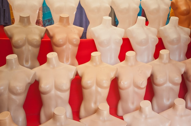 Manequins plásticos despidos brancos no fundo vermelho. Foto Premium