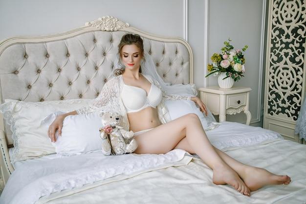Manhã da noiva. a noiva está sentada na cama. bela garota loira sexy, posando de calcinha de renda branca. Foto Premium