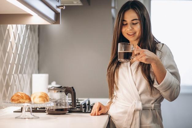 Manhã de mulher com café e croissant Foto gratuita