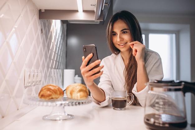 Manhã de mulher com telefone, croissant e café na cozinha Foto gratuita
