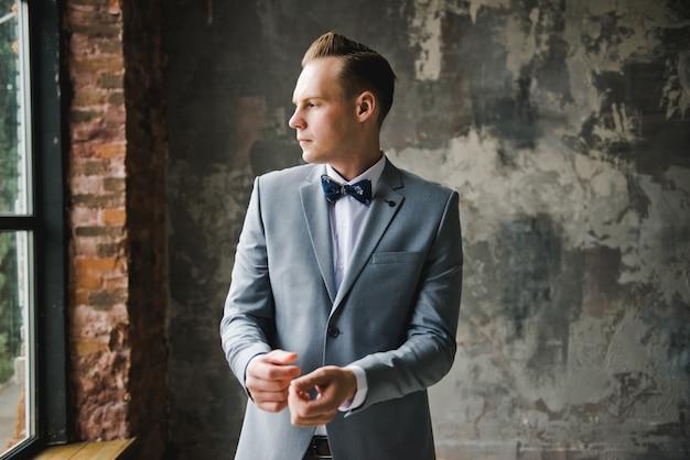 Manhã do noivo. preparação de manhã do noivo. noivo jovem e bonito, vestindo-se Foto Premium