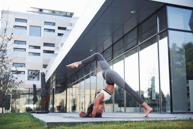 Manhã ensolarada de verão. mulher atlética nova que faz o pino na rua do parque da cidade entre edifícios urbanos modernos. exercício ao ar livre estilo de vida saudável Foto gratuita