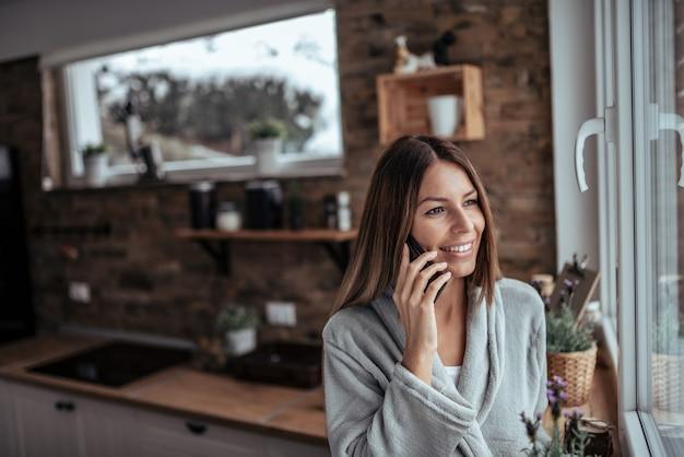 Manhãs de fim de semana. morena bonita que olha através da janela e que fala no telefone esperto no dia de inverno na cozinha acolhedor. Foto Premium
