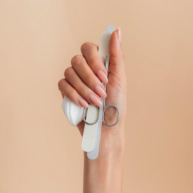 Manicure bonita e saudável segurando acessórios Foto gratuita