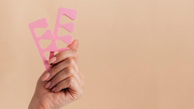 Manicure cuidados saudáveis segurando acessórios de unha rosa Foto Premium