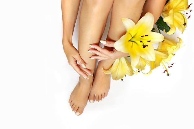 Manicure e pedicure em um longo unhas em forma oval com lírios amarelos sobre um fundo branco. Foto Premium
