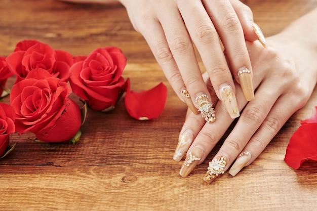 Manicure estilosa e flores rosas Foto Premium