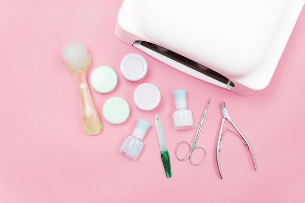 Manicure - ferramentas para criar, polidores de gel, tudo para o tratamento de unhas, o conceito de beleza, cuidados. banner salão fundo rosa Foto Premium