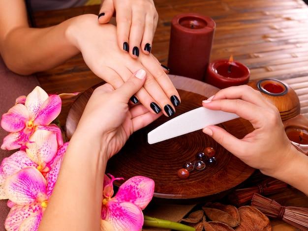 Manicure mestre faz manicure nas mãos da mulher - conceito de tratamento de spa Foto gratuita