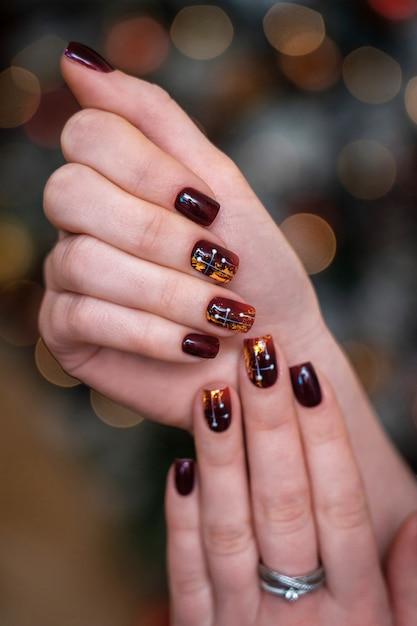 Manicure na moda e bonito nas mãos femininas. unhas carmesim ou borgonha em combinação com brilho dourado. Foto Premium