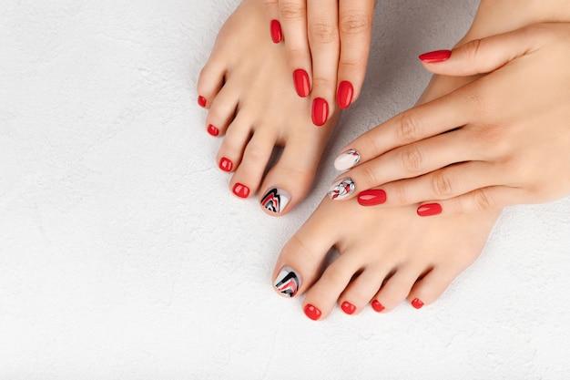 Manicure, pedicure conceito de salão de beleza. mãos e pés da mulher em cinza Foto Premium