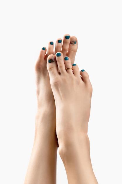 Manicure, pedicure conceito de salão de beleza. os pés da mulher em fundo branco Foto Premium