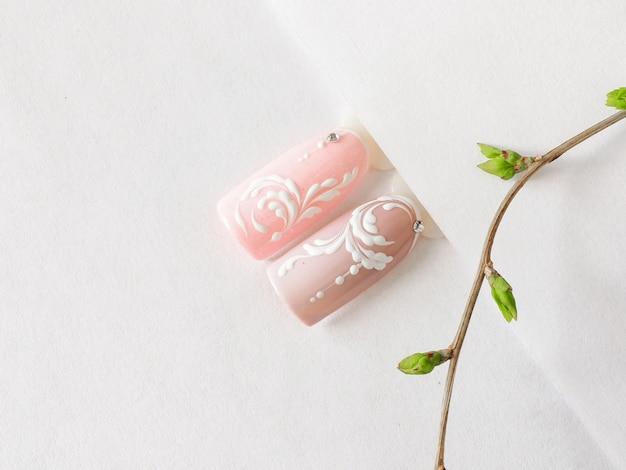 Manicure primavera. dicas com monograma rosa design sobre uma mesa branca. Foto Premium