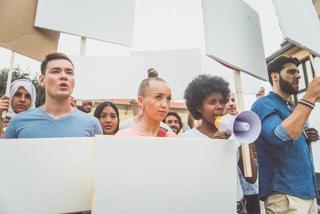 Manifestação pública na rua contra problemas sociais e direitos humanos. grupo de pessoas multiétnicas fazendo protesto público Foto Premium
