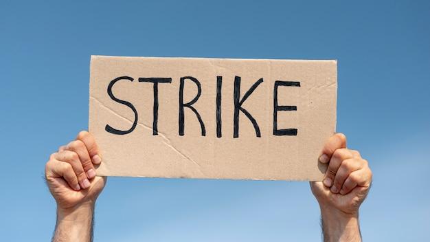 Manifestante segurando placa com greve Foto gratuita
