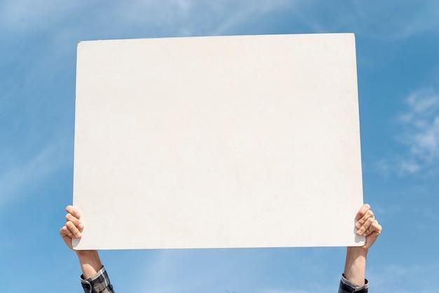 Manifestante segurando placa com maquete Foto Premium