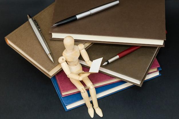 Maniqui leitura sentado em uma montanha de livros e canetas Foto Premium