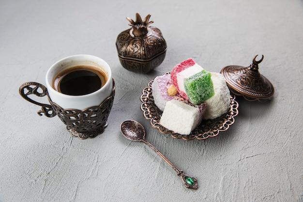 Manjar turco com uma xícara de café na mesa cinza Foto Premium