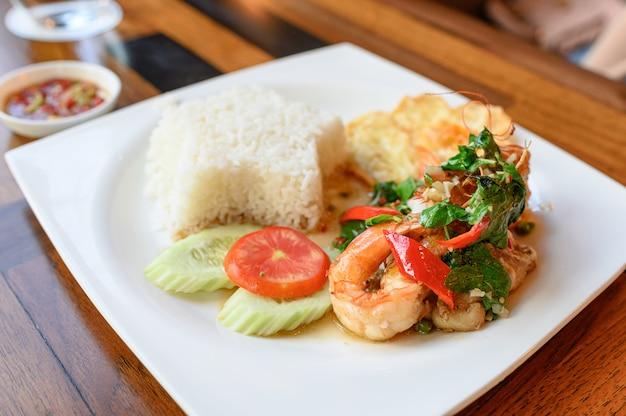 Manjericão frito, chili com camarão, lula com ovo frito e arroz branco Foto Premium