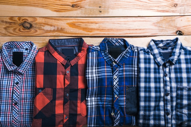 Manta de camisas no plano com fundo de madeira Foto Premium