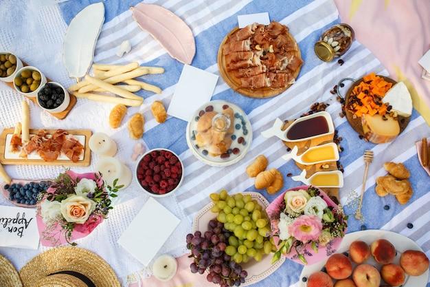 Manta de piquenique de verão com comida saborosa e lanches nele. fins de semana de verão Foto Premium