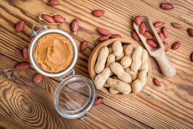Manteiga de amendoim cremosa na mesa de madeira. Foto Premium