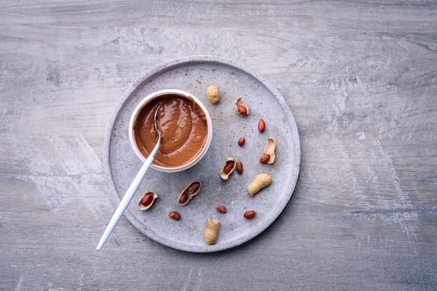 Manteiga de amendoim e amendoins em fundo cinza, vista superior Foto Premium