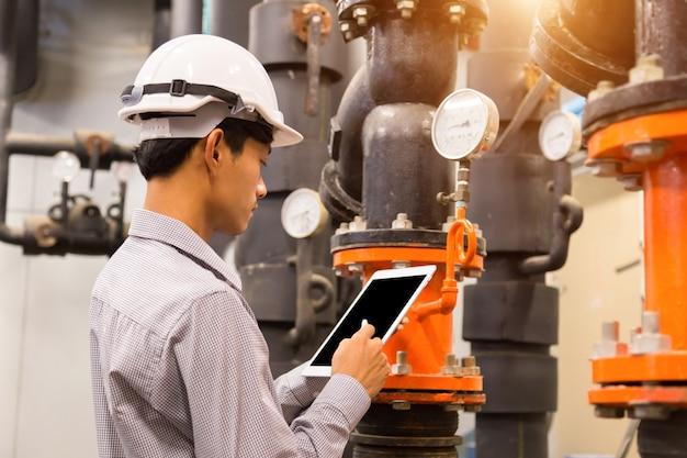 Manutenção de engenheiro asiáticos, verificação de dados técnicos do sistema de equipamentos bomba de água do condensador e manômetro Foto Premium