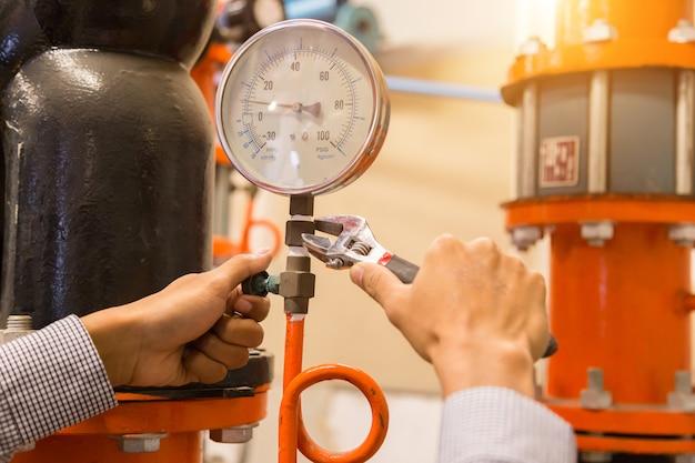 Manutenção de engenheiro asiáticos verificando dados técnicos do equipamento do sistema Foto Premium