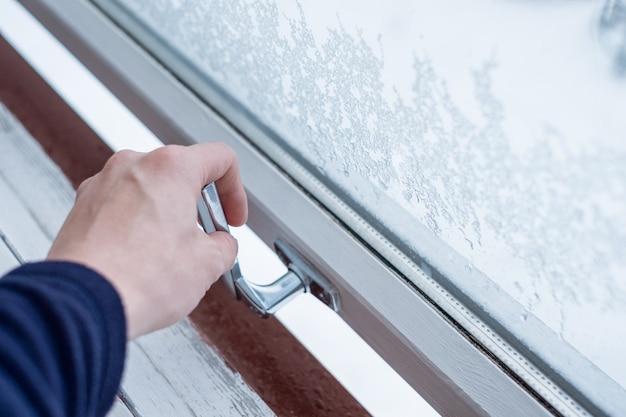 Mão abrindo a janela de bloqueio com flocos de gelo no inverno Foto Premium