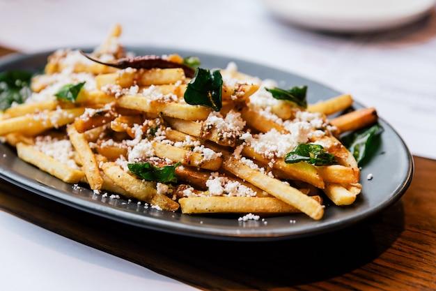 Mão beliscar batatas fritas com manjericão frito Foto Premium