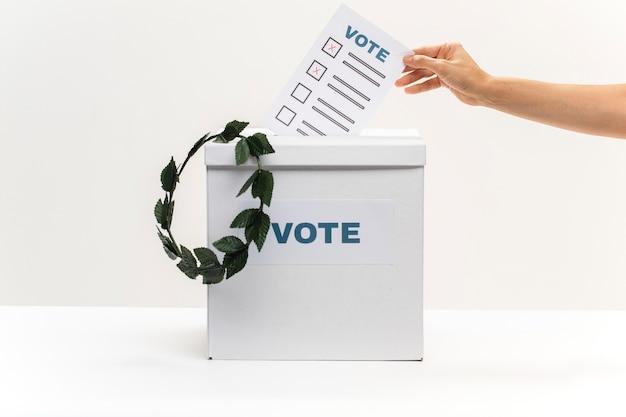Mão coloca boletim de voto na caixa de votação e uma coroa Foto gratuita