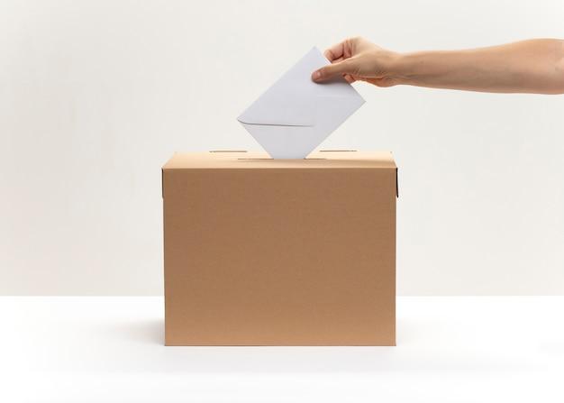 Mão coloca envelope branco na caixa de votação Foto Premium